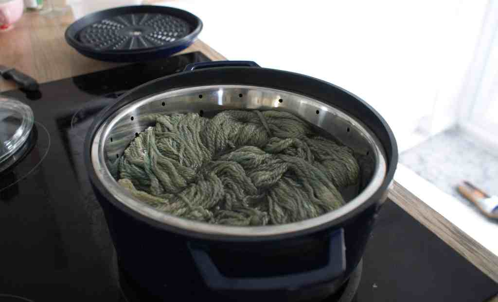 yarn in a pot on the hob soaking in green liquid