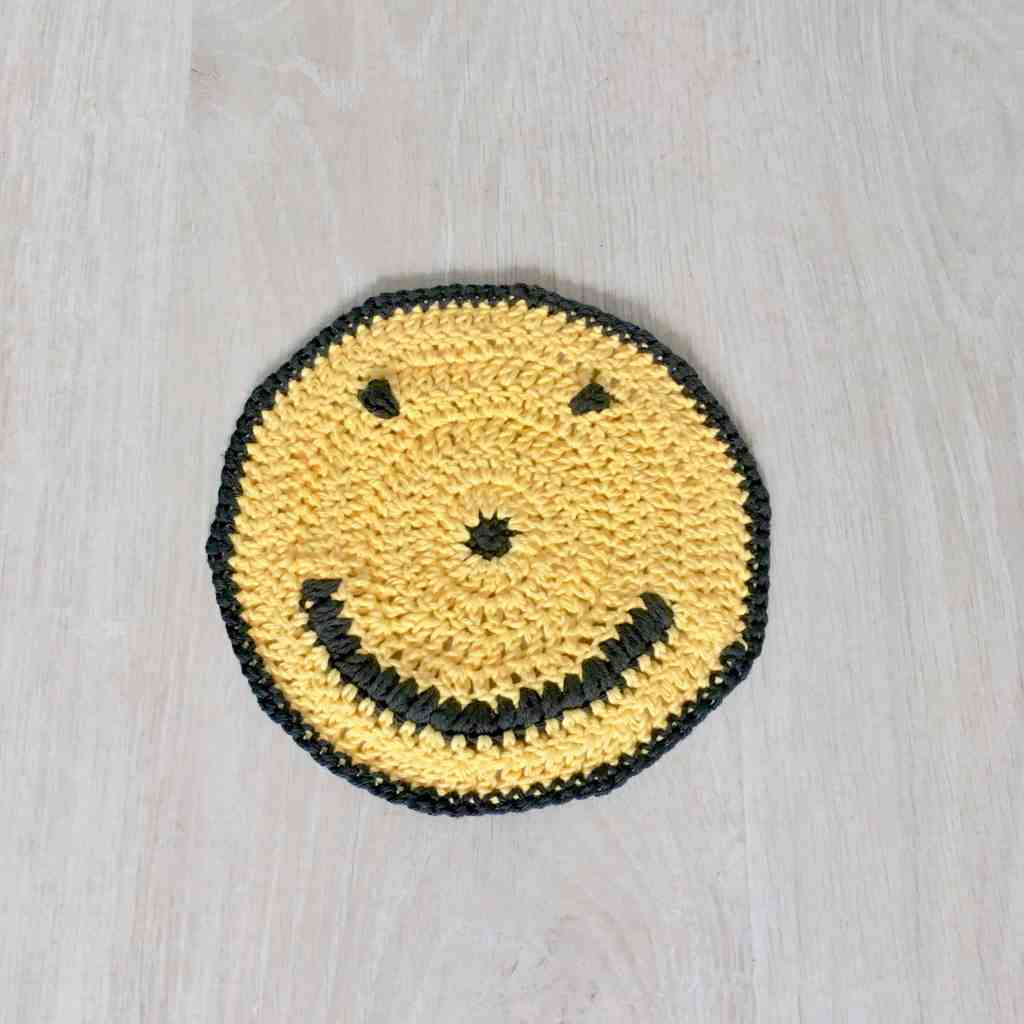 Yellow and black crochet smiley face