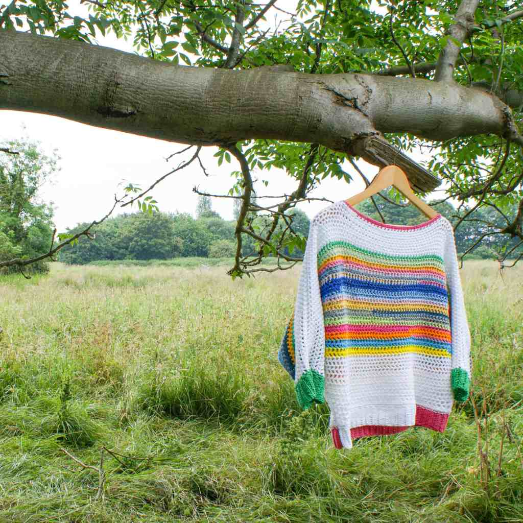 Rainbow striped crochet sweater hanging in tree in field