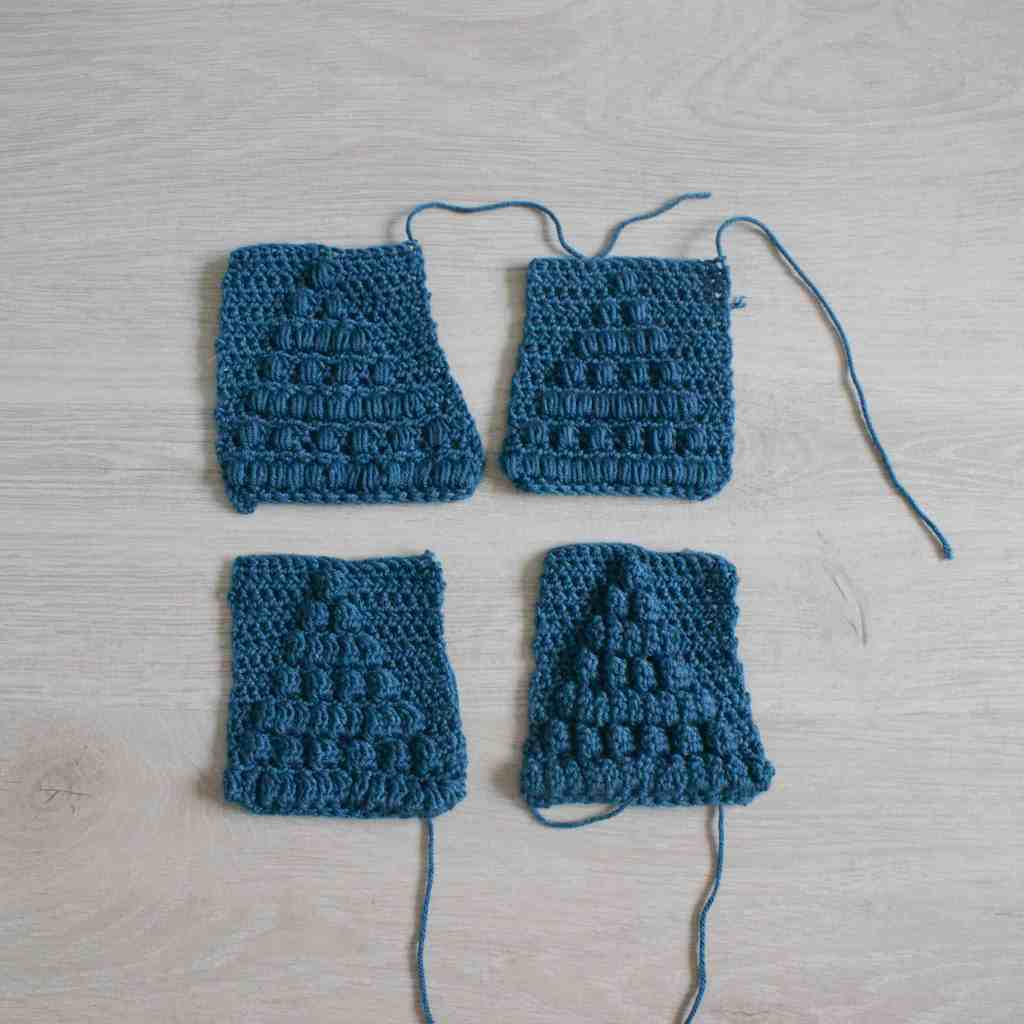 4 blue crochet swatches for bobble, puff, cluster and popcorn stitch on a grey background