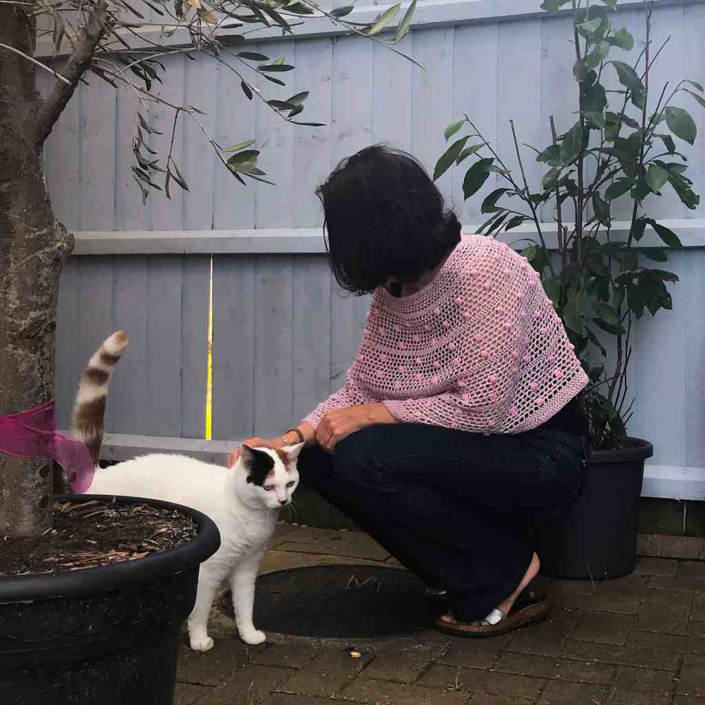 Women wearing pink and green crochet poncho crouching down in garden stroking a white cat