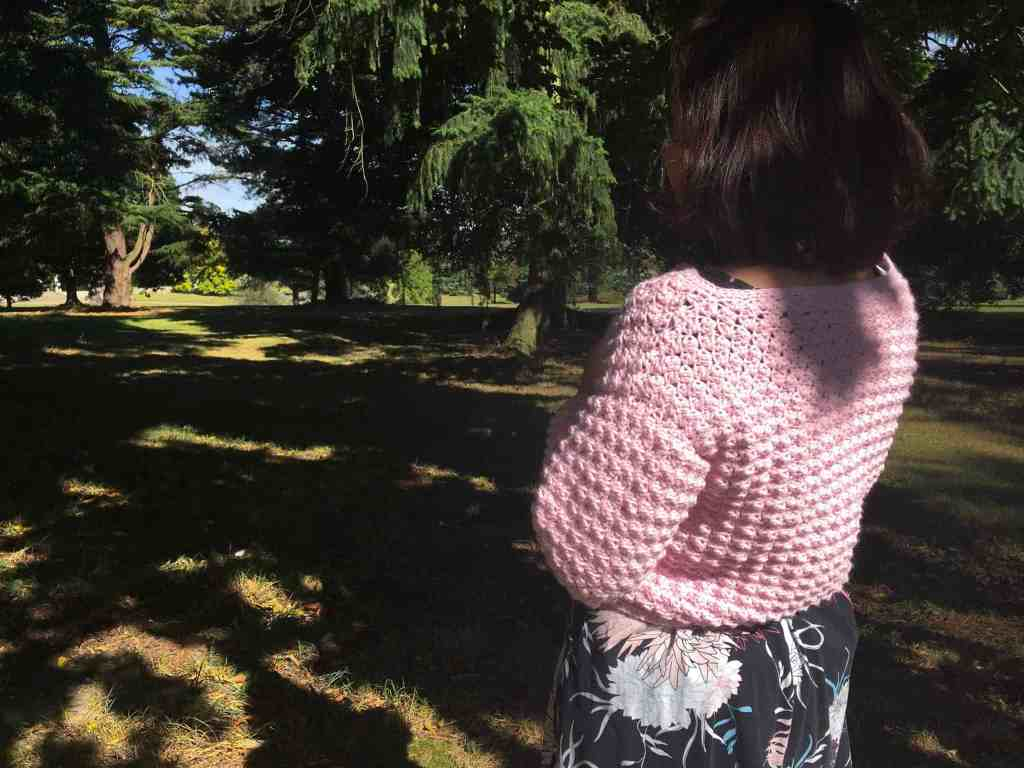 Woman in pink crochet cardigan standing in gardens with back to camera