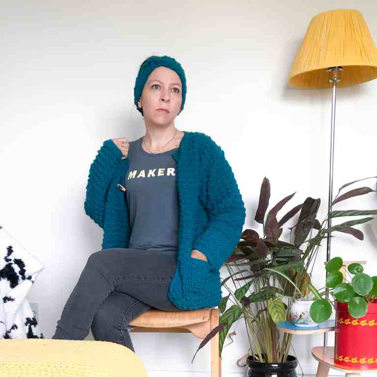Woman in teal crochet textured cardigan and maker slogan tee sat on wooden seat in front of white wall