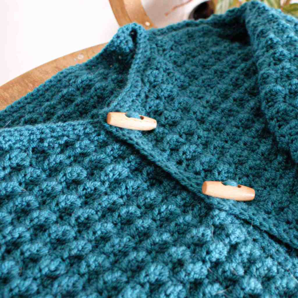 Close up of teal crochet cardigan with duffel wood buttons