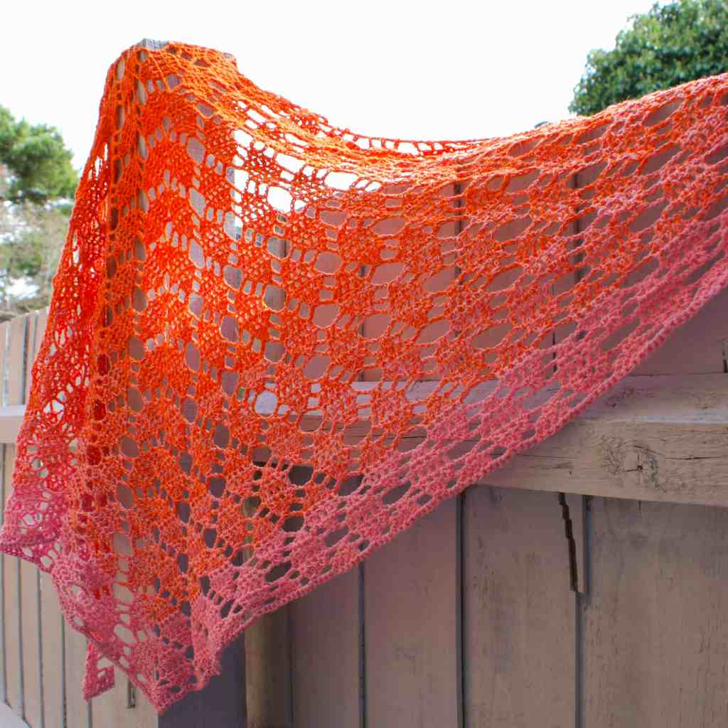 Pink and orange crochet shawl hanging on fence