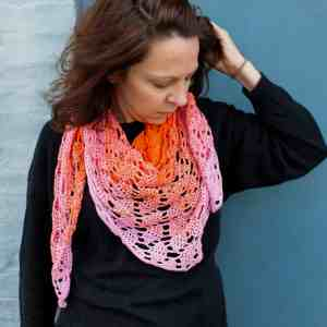 Woman standing in front of blue door wearing pink and orange crochet scarf over a black sweater
