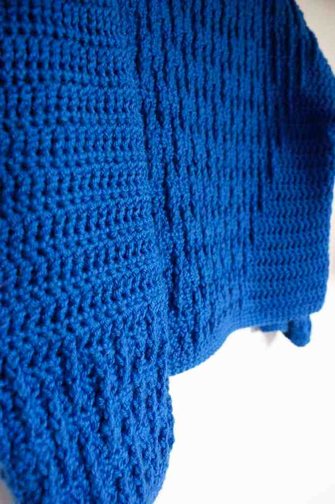Close up of blue crochet sweater hanging on wall