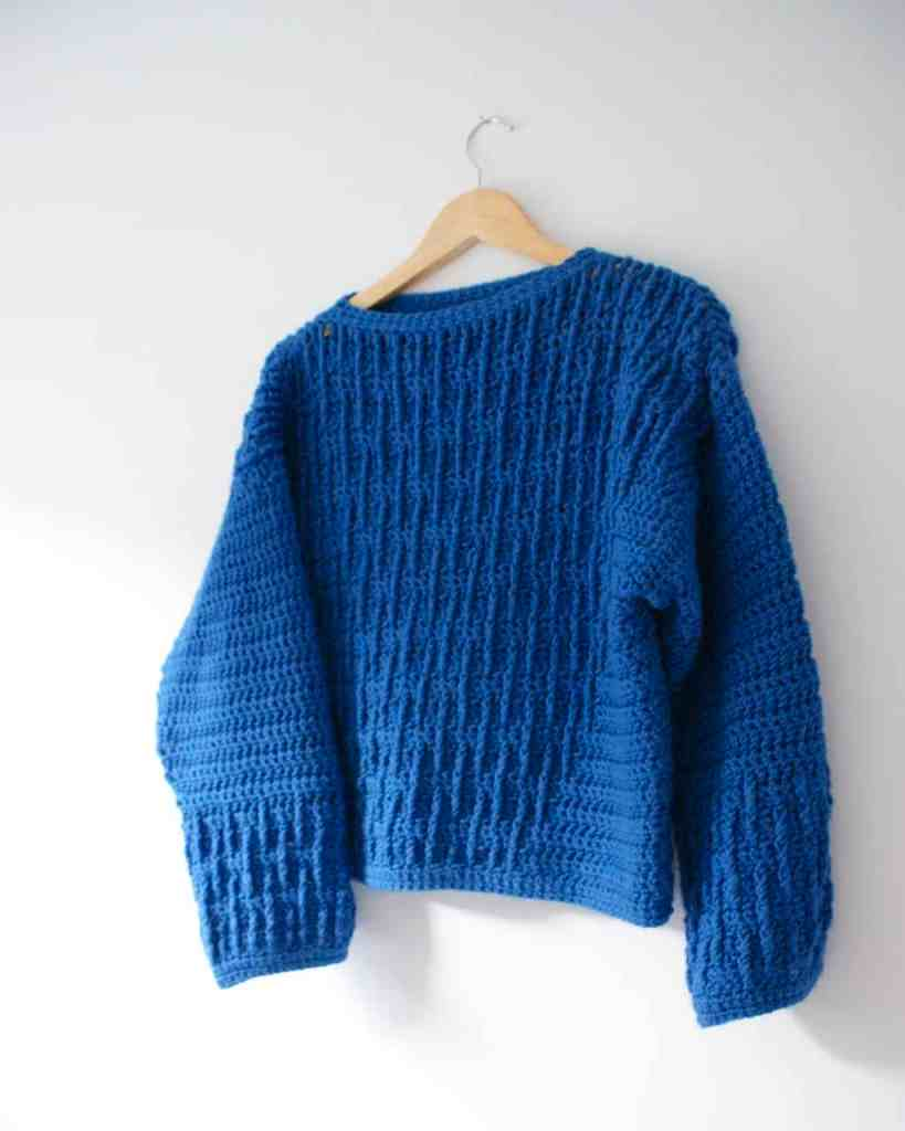 Blue textured crochet sweater on hangar on white wall