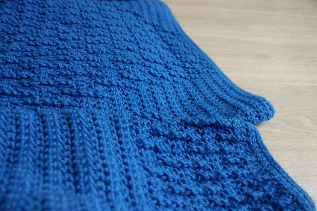 Close up of texture of blue crochet jumper on grey floor