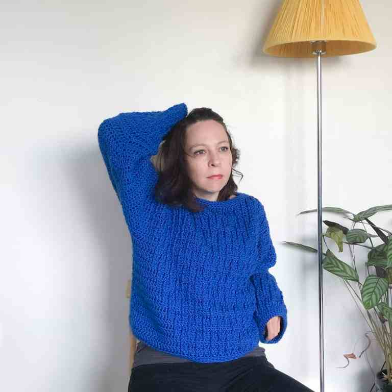 Woman in blue crochet sweater sitting on a wooden stool in front of white wall next to yellow light stand