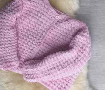 Pink crochet cardigan laying on sheepskin rug