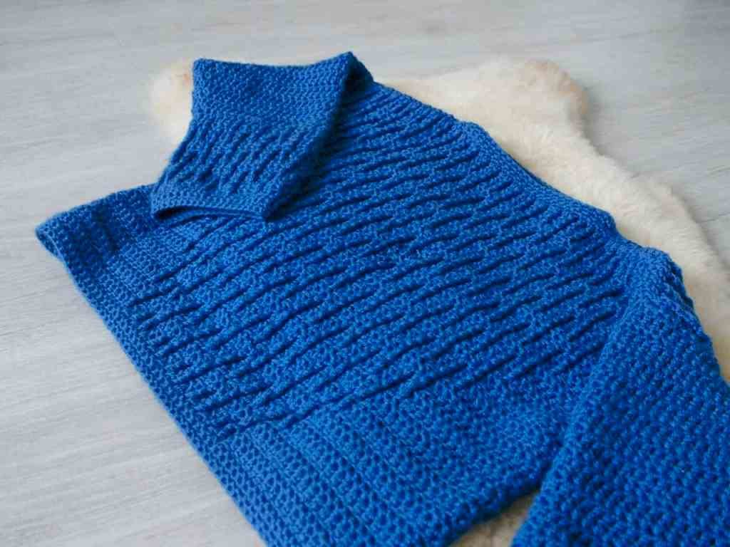 Blue textured crochet sweater on sheepskin rug on grey floor