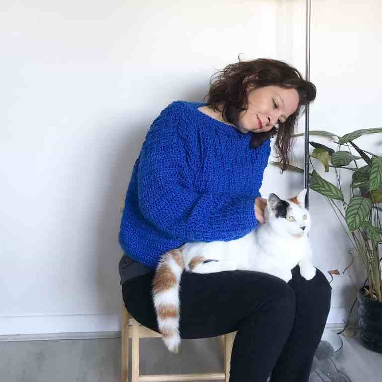 Woman in blue crochet sweater sitting on a wooden stool in front of white wall with cat on her lap