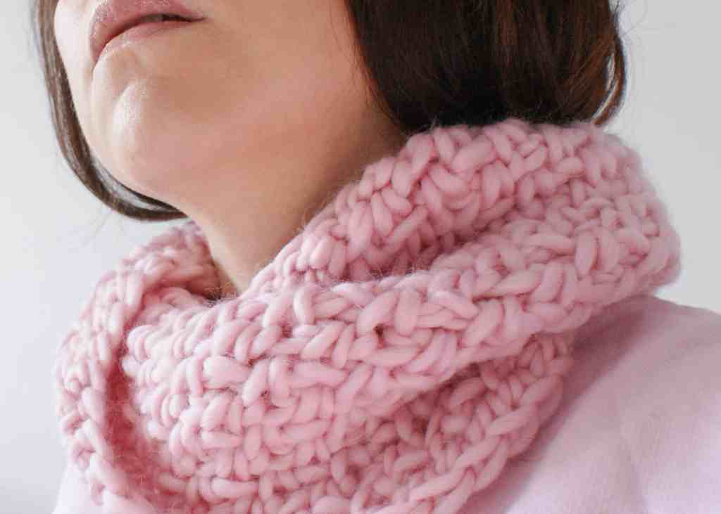 Woman wearing pink crochet twisted cowl and pink sweater