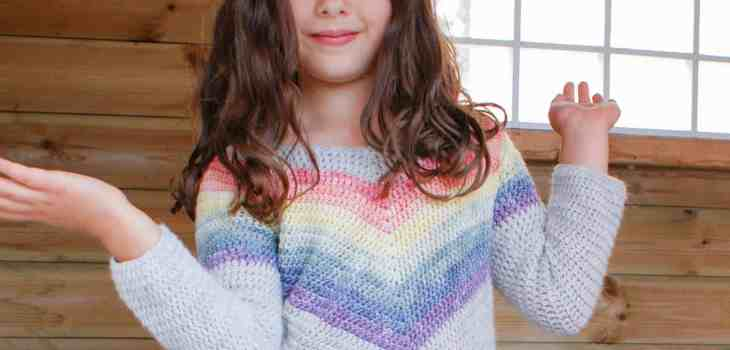 Girl wearing crochet rainbow chevron sweater in playhouse