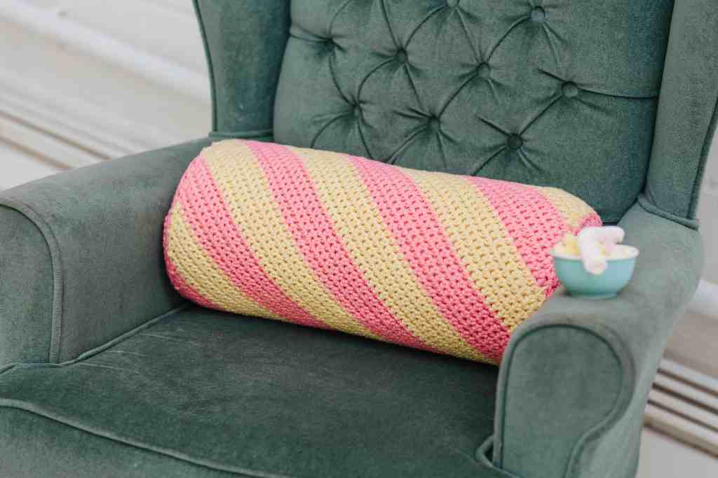 Pink and yellow flump style crochet bolster cushion on velvet green armchair