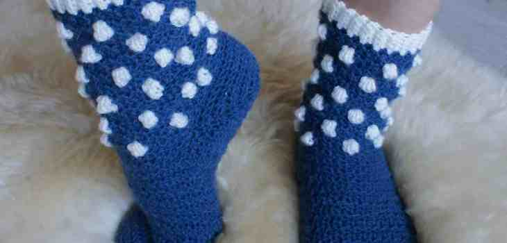 Picture of feet in blue socks with white bobbles on the ankle imitating snowballs