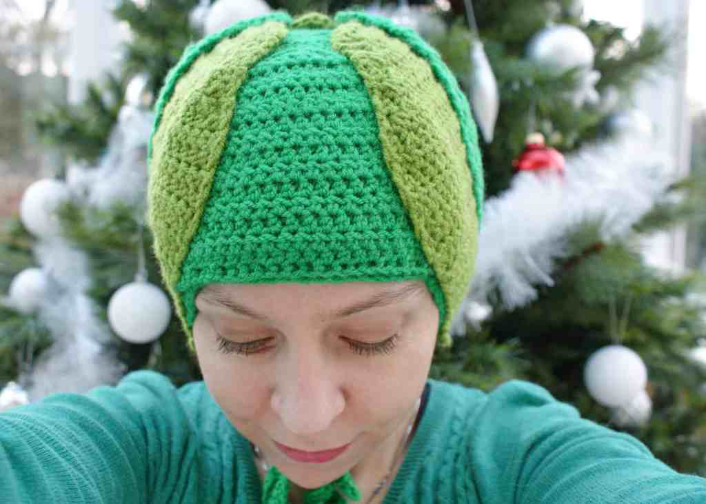 Crochet Brussel sprout hat worn by woman in front of a christmas strr