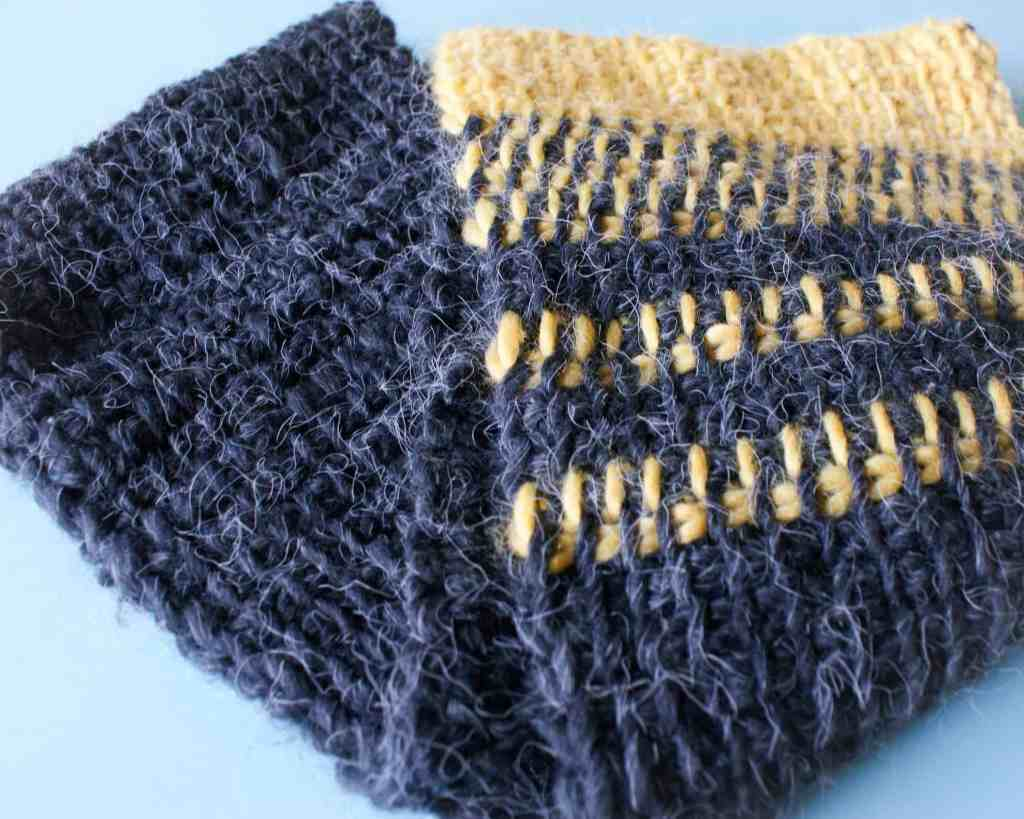 Yellow and charcoal grey tunisian simple stitch infinity scarf on blue background