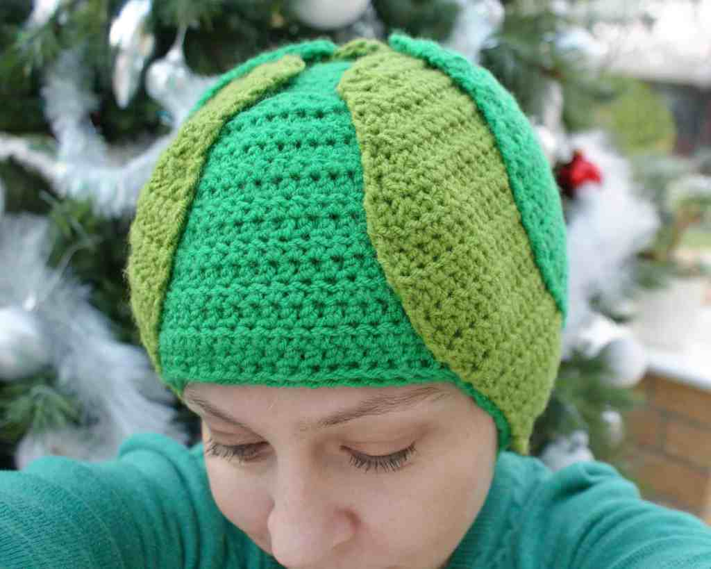 Selfie of woman wearing crochet Brussels sprout hat in front of a christmas tree