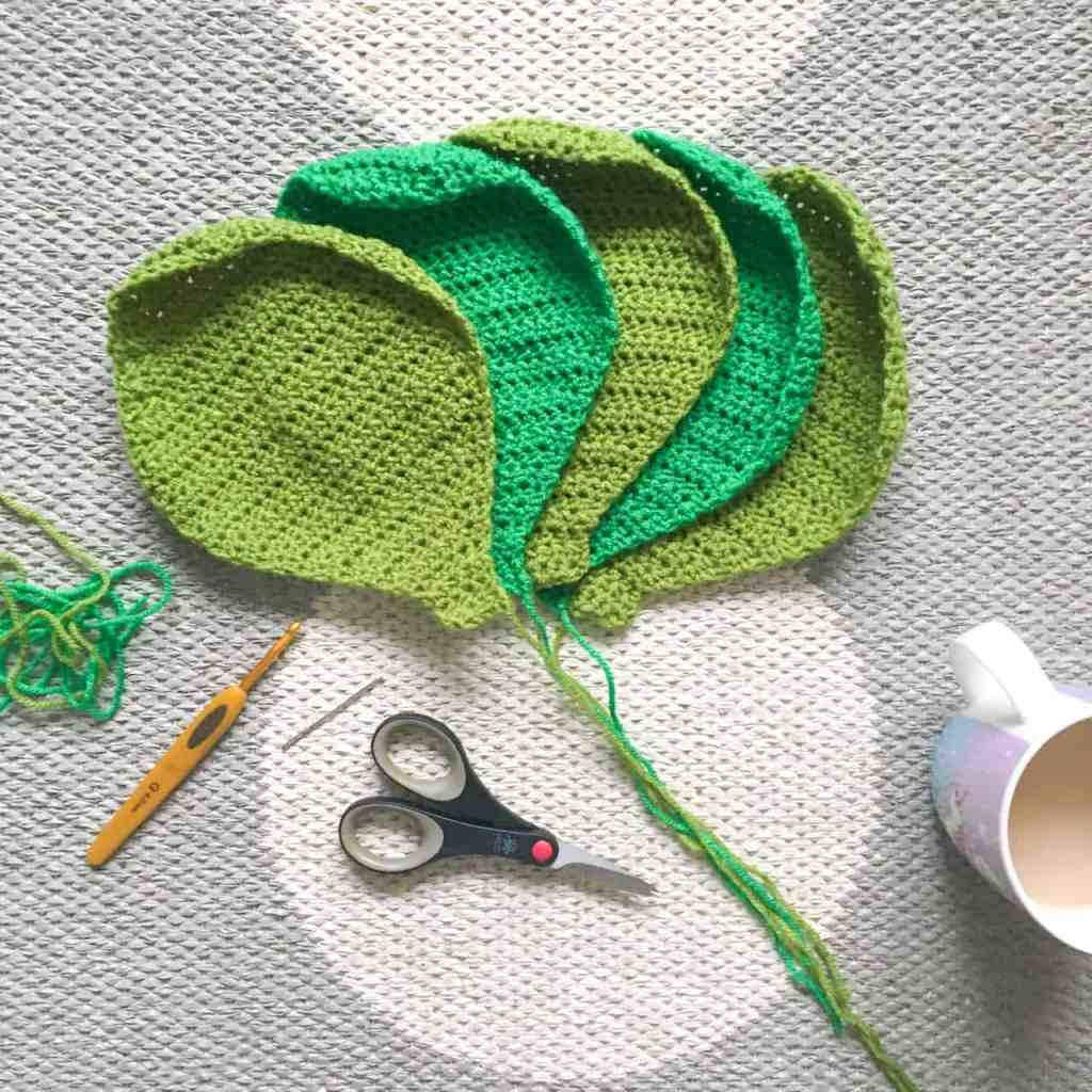 Green Crochet sprout leaves laid out on rug with scissors crochet hook and cup of tea