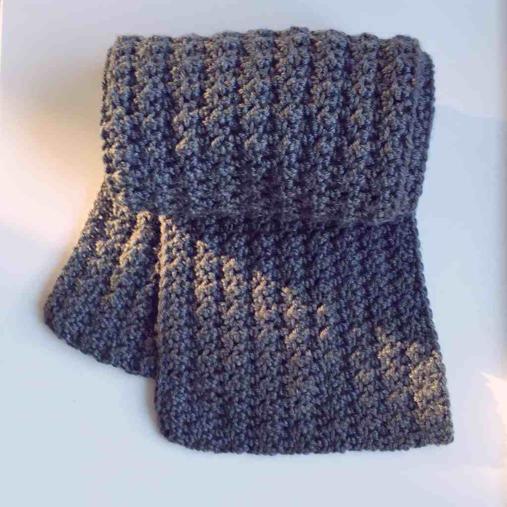Grey textured crochet scarf rolled up on white background with sunbeam falling on it