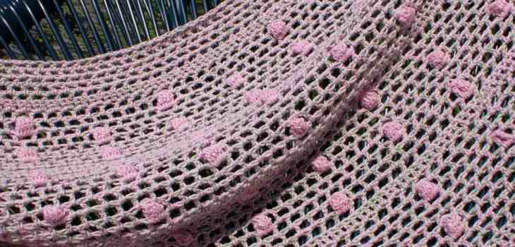Crochet poncho draped over chair in front of Lavendar bush