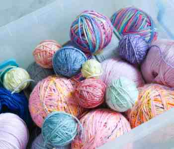 Multi coloured balls of yarn in a plastic storage box