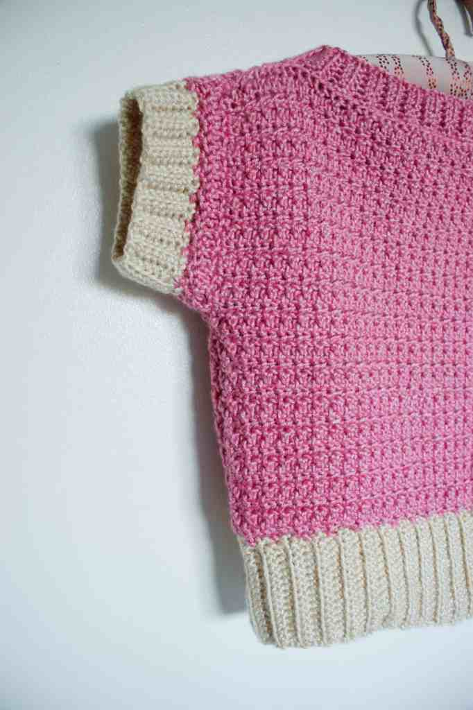 Half of a pink and cream crochet sweater hanging on a white wall