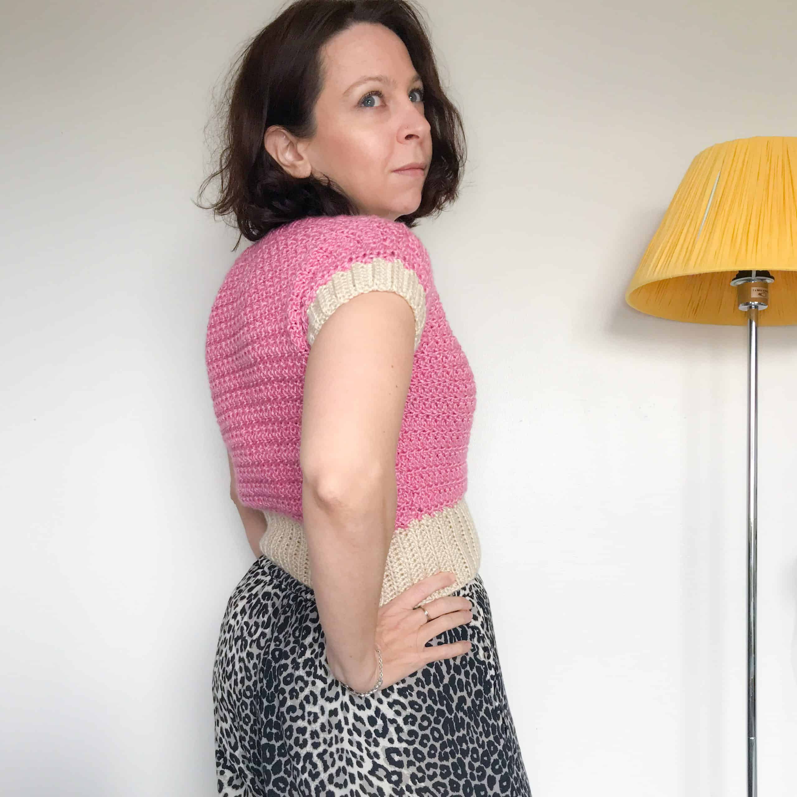 woman standing side onto the camera in front of a white wall, wearing a pink and cream crochet t-shirt and leopard print trousers. There is a yellow standing lamp behind her