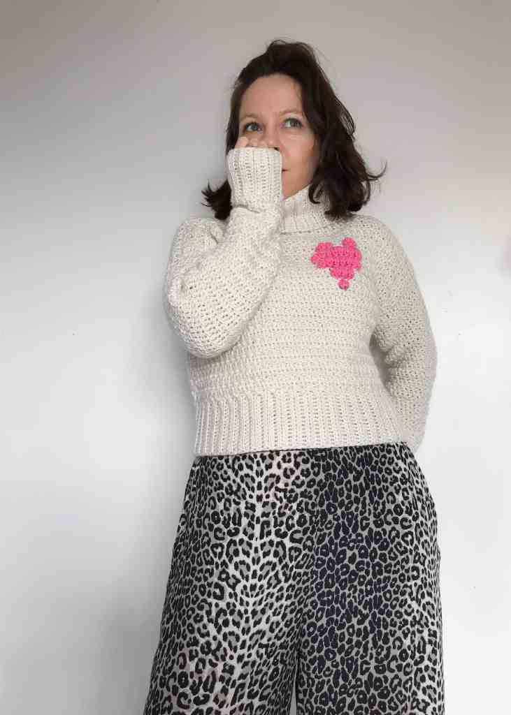 Woman wearing a roll neck crochet sweater with a pink heart motif. Her hand is to her mouth as she stands in front of a white wall
