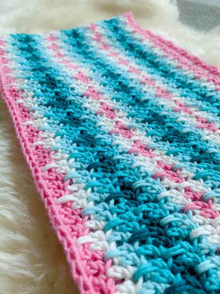 Pink, White Blue and Turquoise stripe crochet infinity scarf on a sheepskin rug