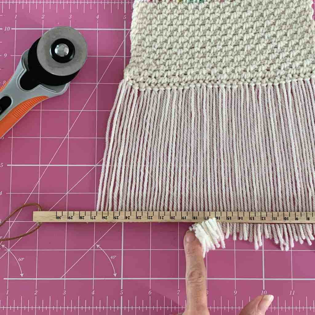 A finger wipes away the cut ends of a scarf fringe as it lies on a pink cutting mat with the rotary trimmer placed to the side