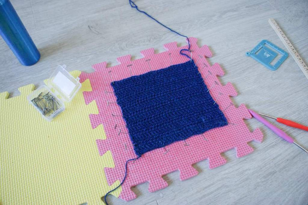 Blue crochet swatch pinned out on pink foam board with blocking and crochet accessories spread around