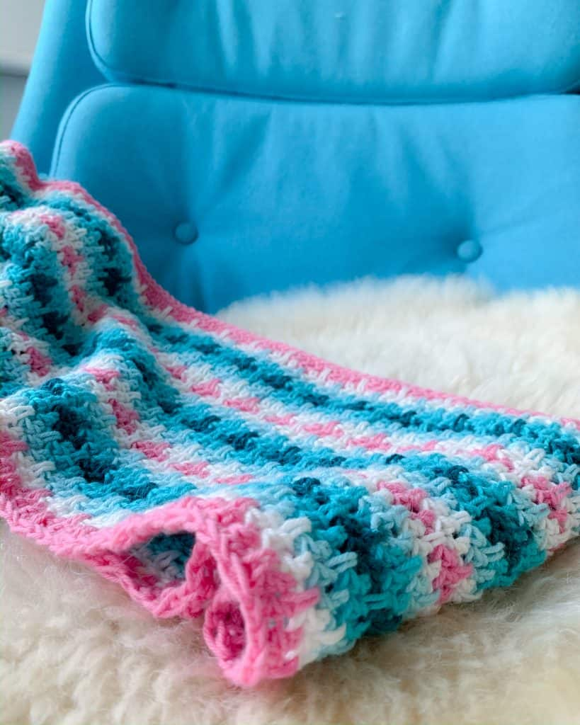 striped crochet infinity scarf on a sheepskin pelt on the seat of a blue lounge chair