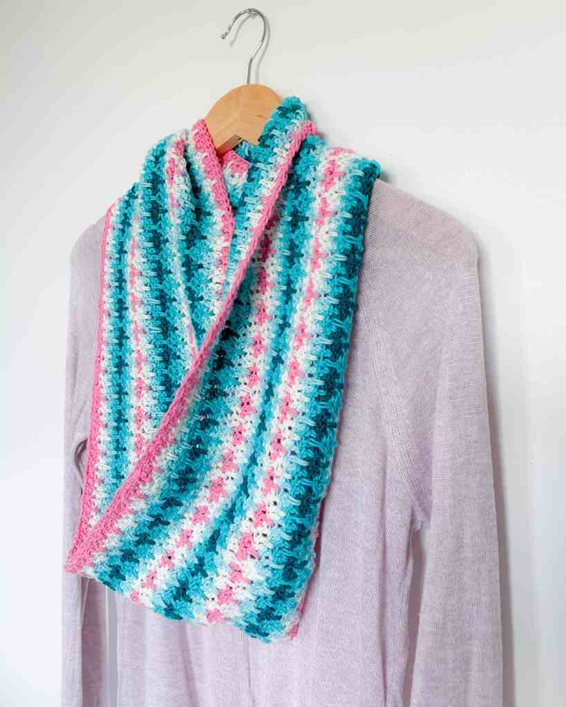 Pink, White Blue and Turquoise stripe crochet infinity scarf on a hanger with a sweater hanging from it from side angle