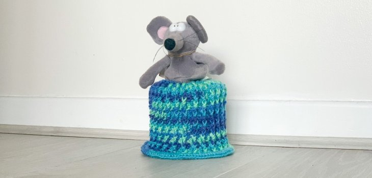 A crochet loo roll pattern with a rat in a skirt