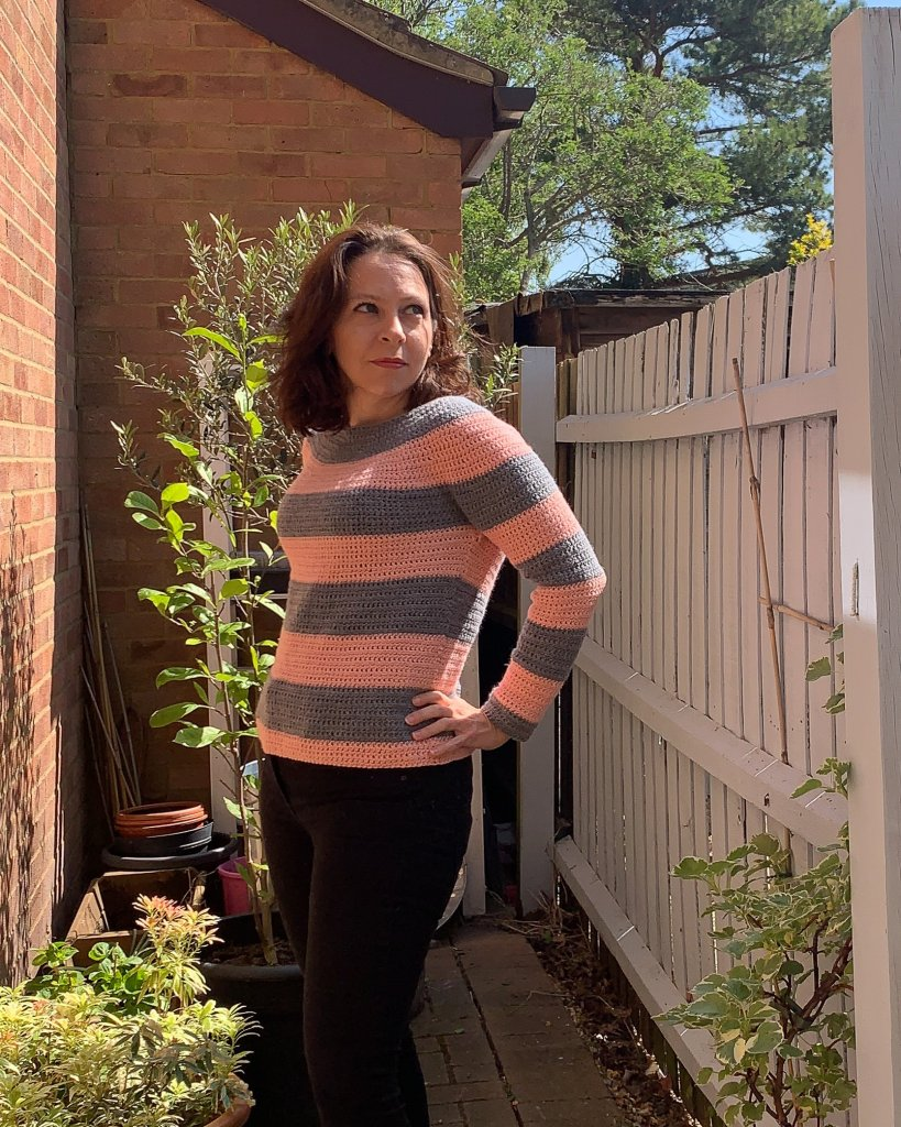 A woman models a pink and grey striped crochet sweater in front of a walled garden