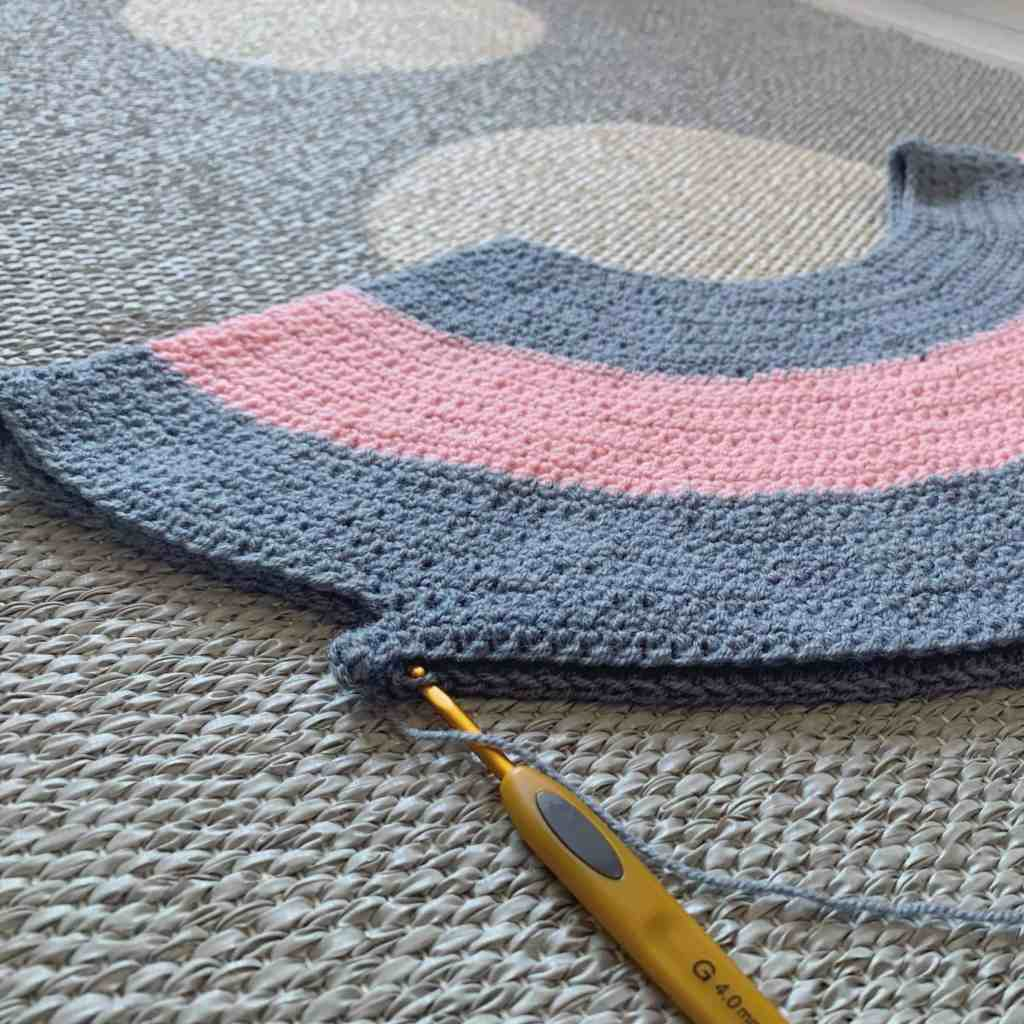 close up of the split yoke of a grey and pink striped crochet sweater in progress