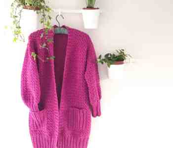 A long chunky pink crochet cardigan with ribbed pockets hangs on a white wall surrounded by plants