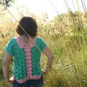 A woman stands back to camera with her hands on hips in a grass land wearing a pink and green triangle motif crochet top