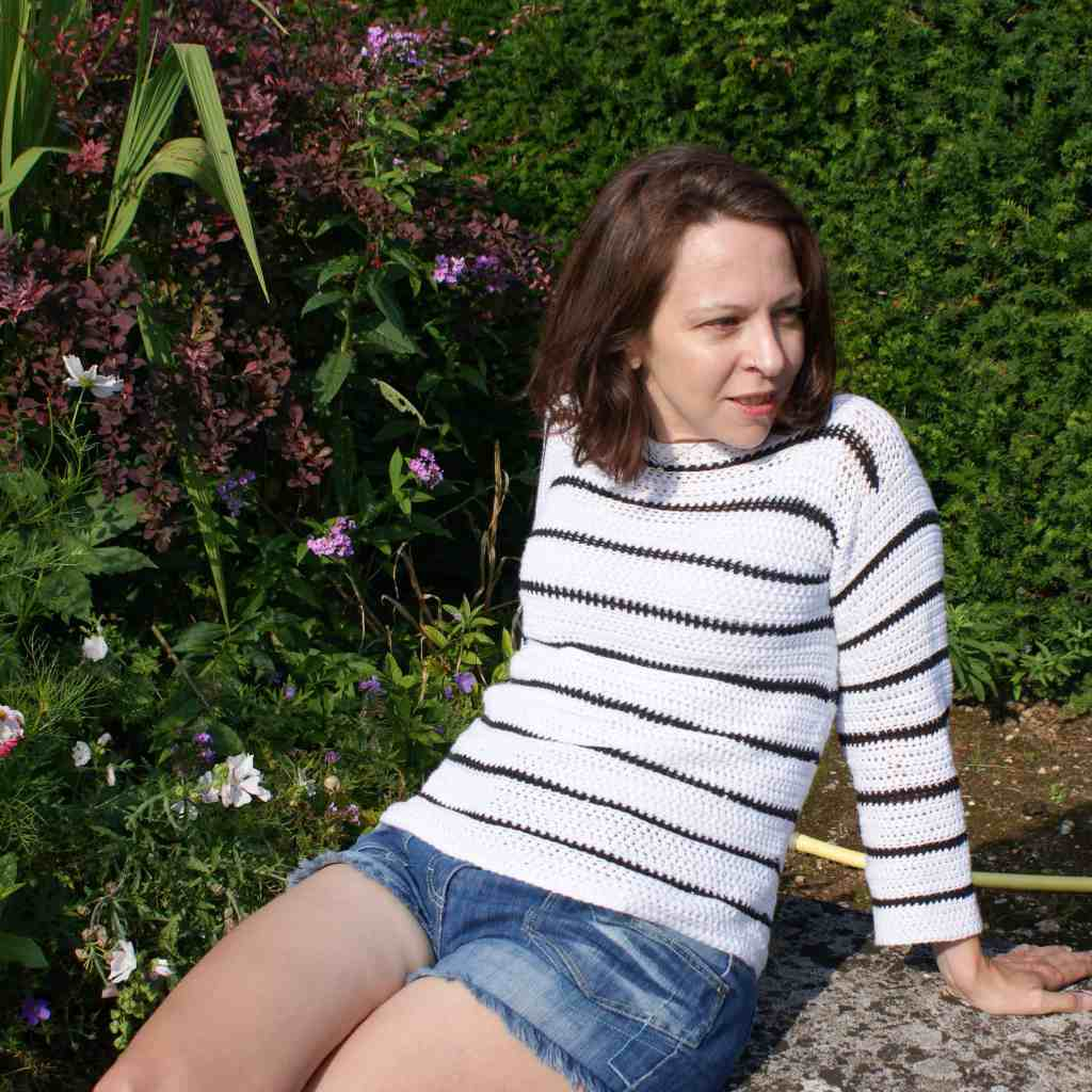 A woman sits on a stone bench in a flower garden leaning back on her hands whilst wearing denim shorts and a white crochet sweater with black strips
