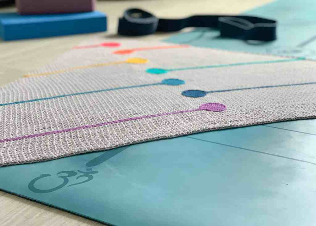 The crochet chakra shawl lies on a yoga mat with a yoga strap and blocks out of focus in the background