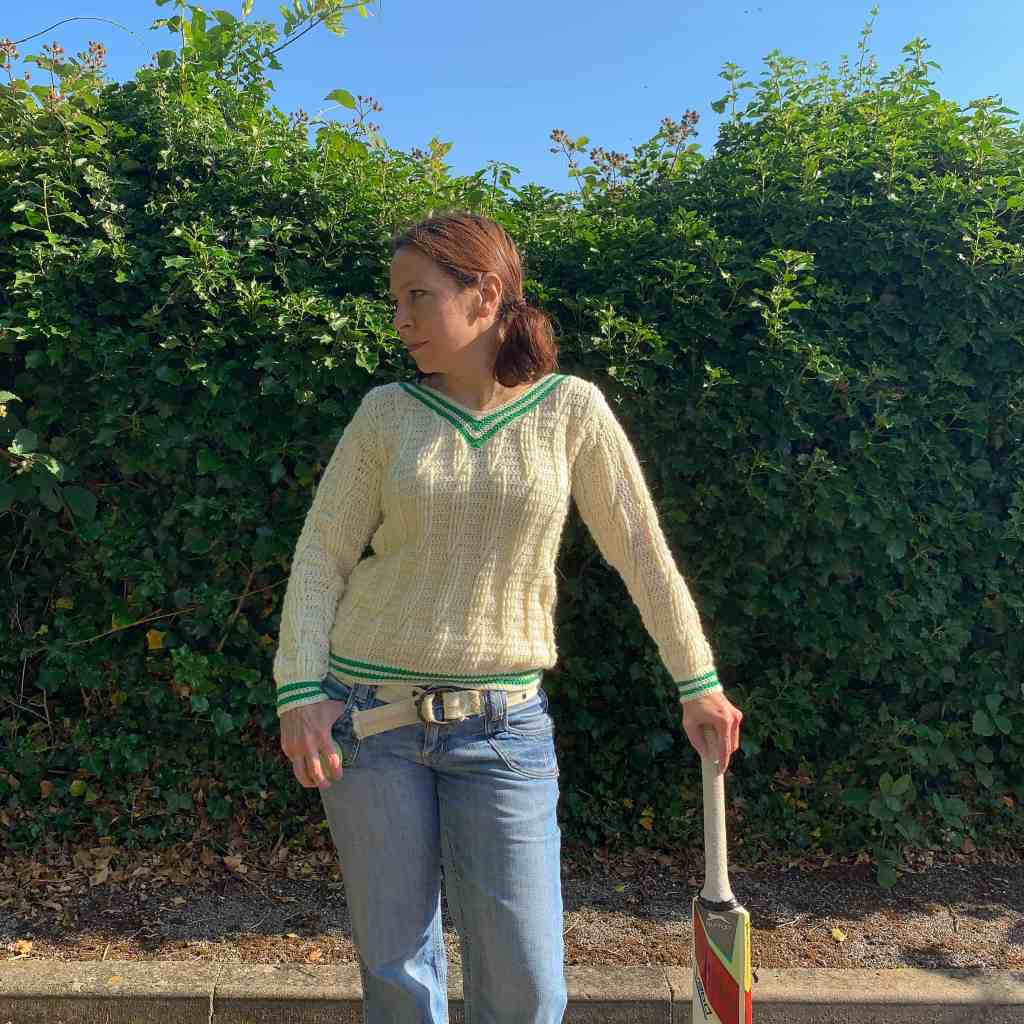 A woman standing in front of a hedgerow wears a cream cabled crochet sweater, with green stripes on the v-neck, cuffs and hem. She leans on a cricket bat and looks to the side