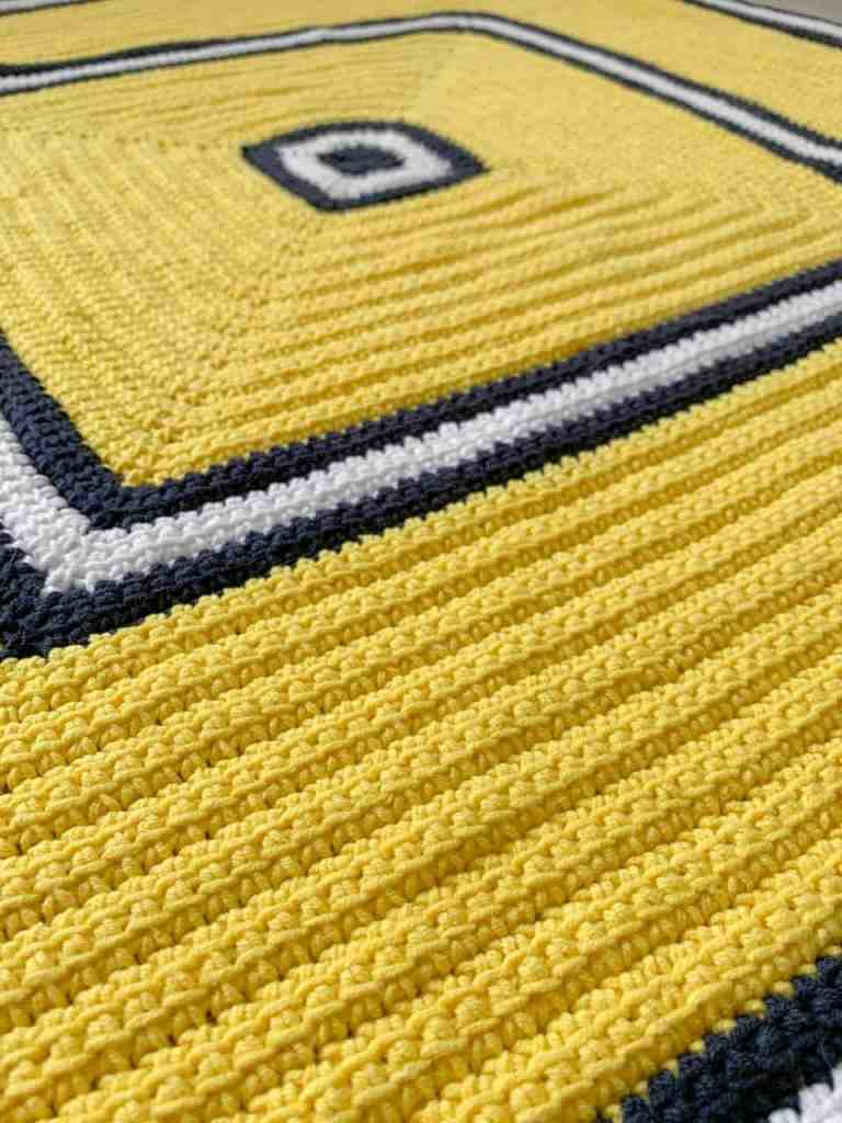 A textured square crochet blanket, yellow with navy and white stripes lies on a flat surface