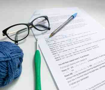 A close up of a crochet pattern laying on a white desk with a pair of glasses, ball of yarn and crochet hook next to it. A pen lies on top and has been used to circle stitches