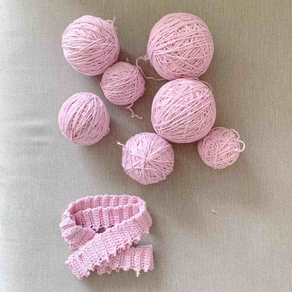 7 balls of yarn of varying size, lie on a grey background with the neckline of what once was a poncho placed next to them