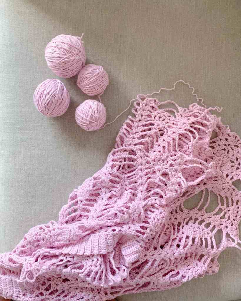 a lacy pink poncho is being unraveled and the yarn which made it lays in balls to the side