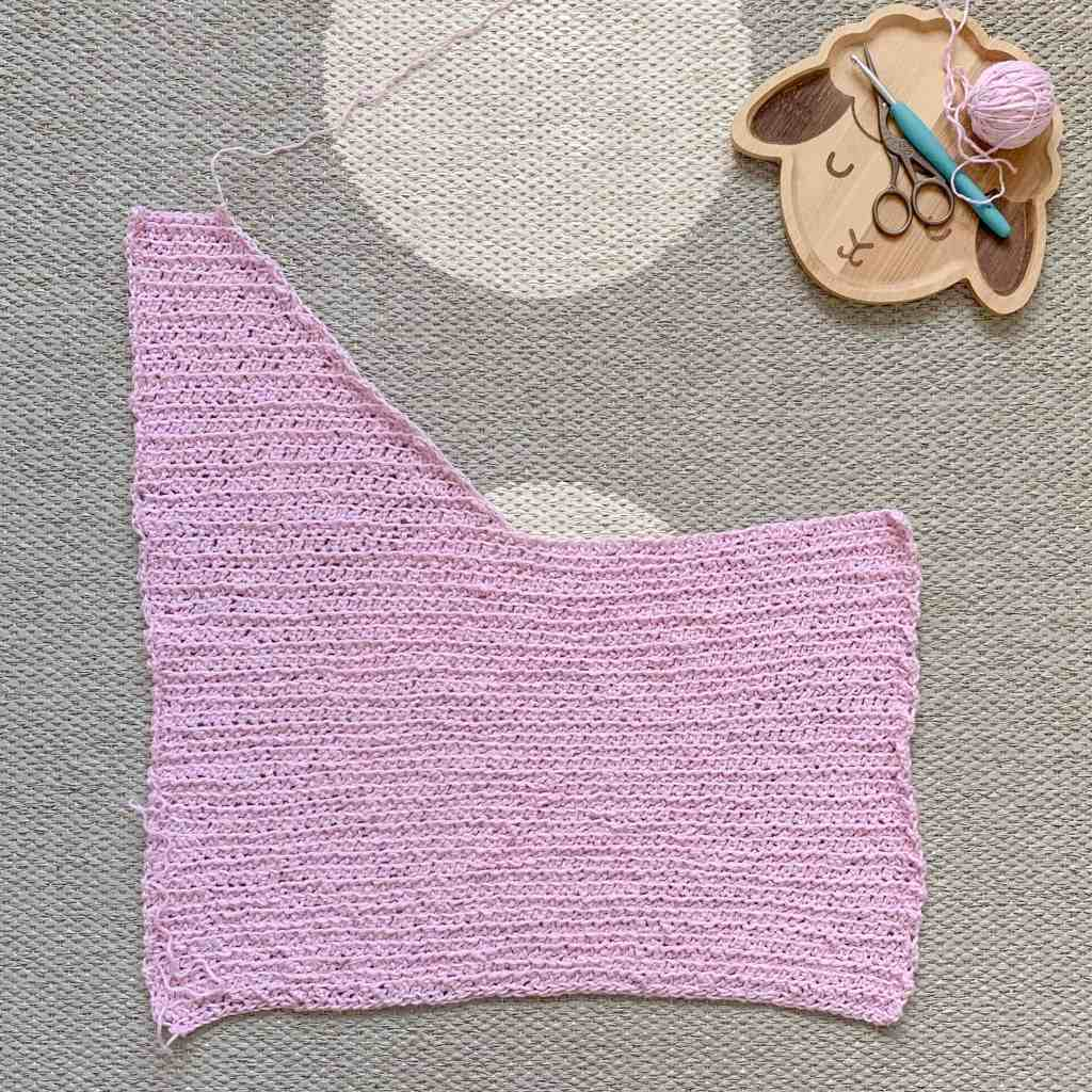 a panel of the crochet top with one side of the shoulder shaping complete lies on a mat with a sheep face plate containing yarn crochet hook and scissors lays to the side
