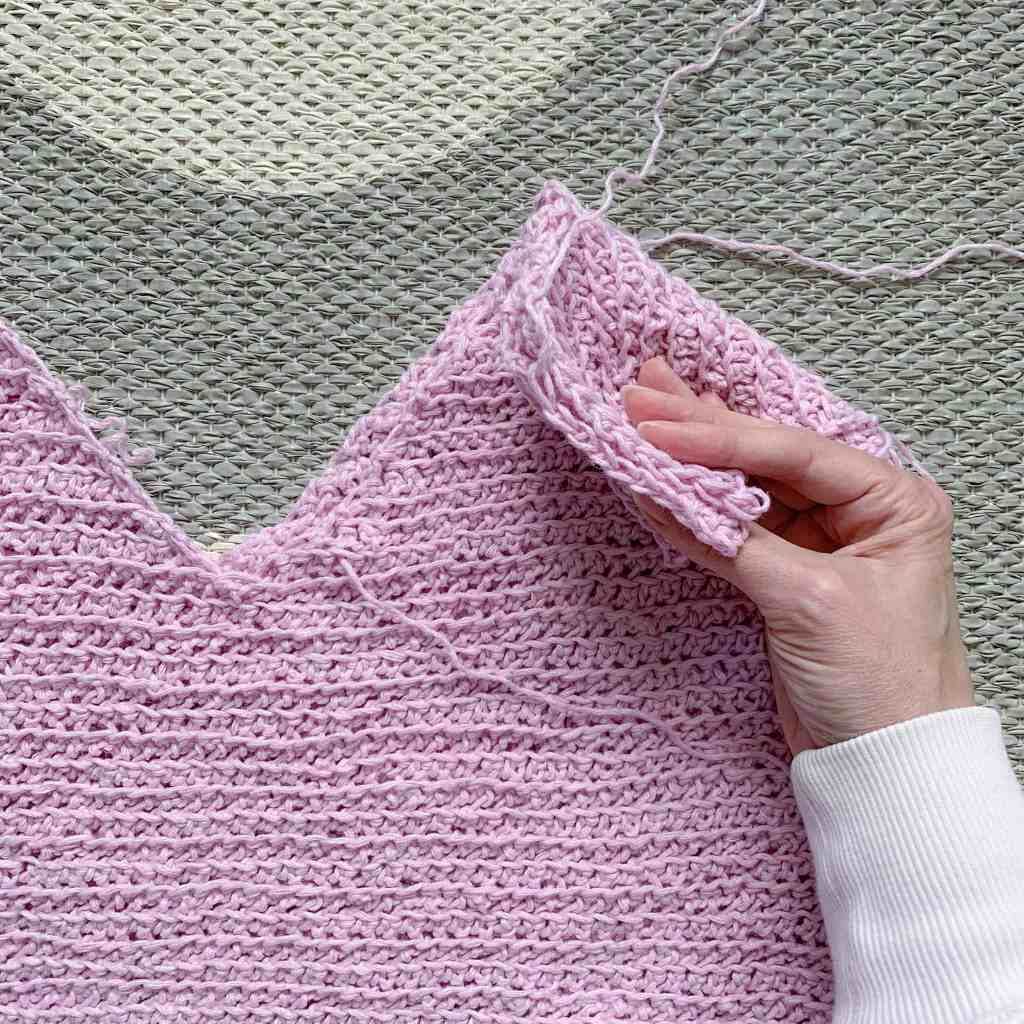 two crochet panels laid together with a hand holding the tops together showing where the shoulder seam will be made